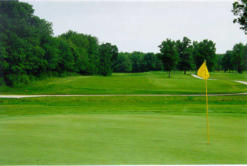 A view of a hole with a cart path in background at Oaktree Golf Course