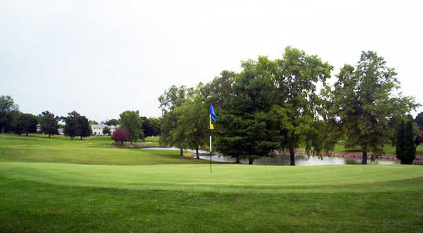 A view of a green with water in background at Delbrook Golf Club