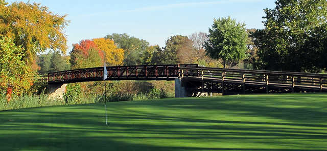 A view of a green with a bridge in background at Pine Hills Golf Club