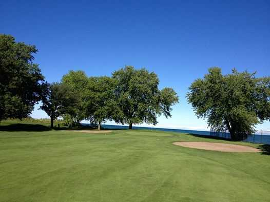 A view of a green guarded by bunkers at South Shore Golf Club