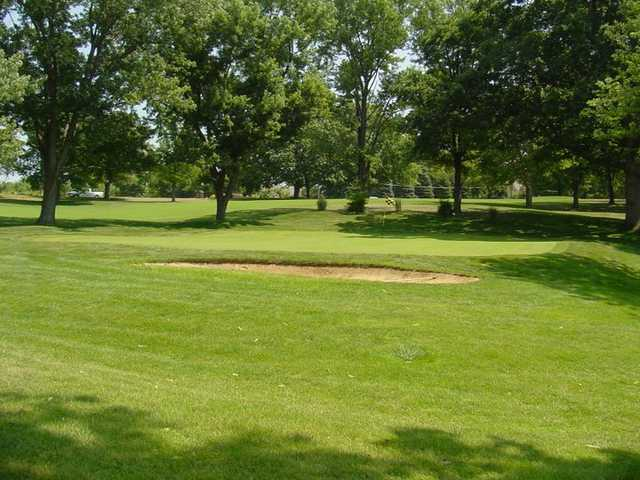 A view of a green protected by a bunker at Hannibal Country Club