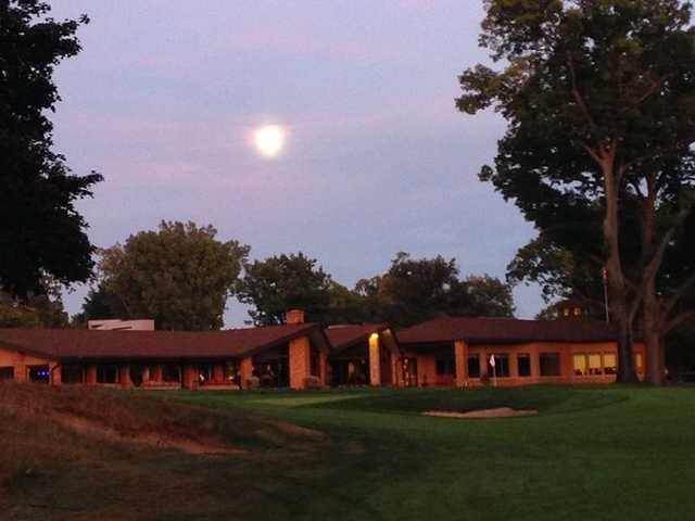 An evening view of a green and the clubhouse at Port Huron Golf Club