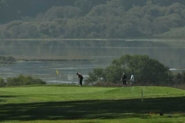 A view of a green with water in background at Pajaro Valley Golf Club