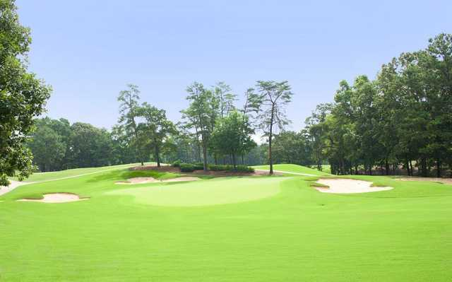 A view of a green flanked by sand traps at Pine Tree Country Club