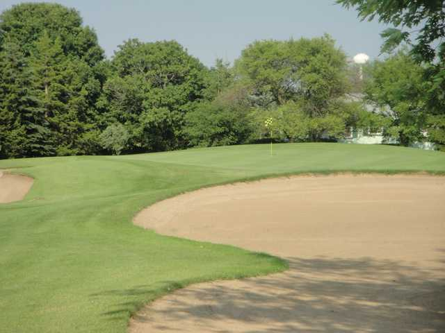 A view of green surrounded by bunkers at Village Green Country Club