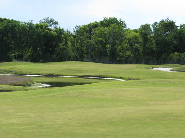 A view of a green protected by a bunker at Rio Colorado Golf Course