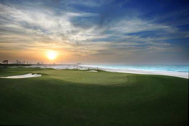 A sunny day view of a hole at Saadiyat Beach Golf Club