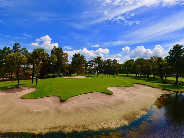 A view of a green with water and sand traps coming into play at Bradenton Country Club
