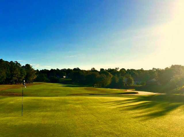 A sunny day view of a green at Kings Ridge Golf Club