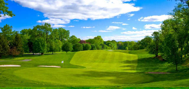 A sunny day view of a hole protected by bunkers at Galloping Hill Golf Course