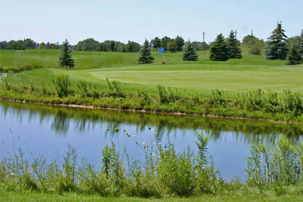 A view over the water of the 16 green at Whispering Ridge Golf Course