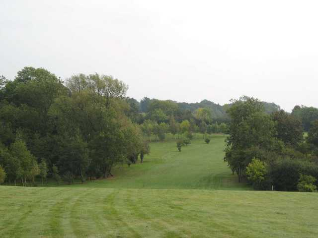 Down hill view of a fairway approaching the green at Gaudet Luce Golf Club