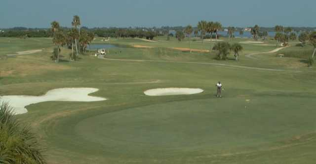 A view of a green protected by sand traps at Cocoa Beach Country Club with narrow road on the left