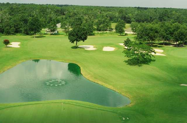 A view of a green with water in background at Wildwood Country Club