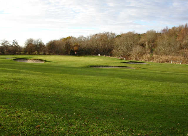 A view of a green surrounded by a collection of bunkers at Bridgend Golf Club