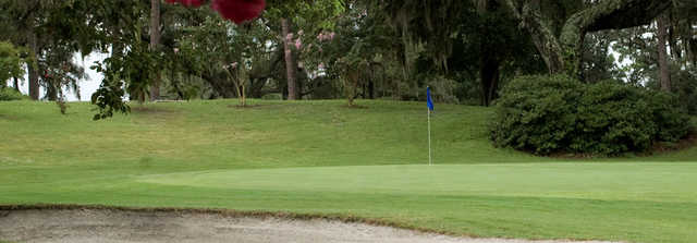 A view of green with bunker in foreground at Deland Country Club
