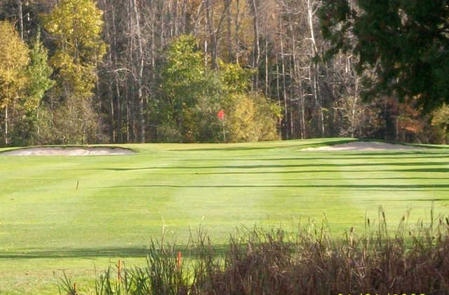 A view of a green flanked by bunkers at Clear Springs Golf Course