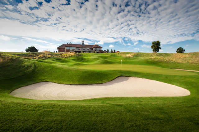 View of a bunkered green with the clubhouse in the background at The Oxfordshire Golf Club