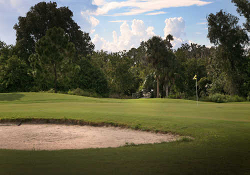 A view of a green with bunker in foreground at Riverside Golf Course