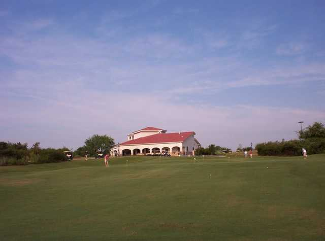 A view of the clubhouse with putting green in foreground at Tierra Verde Golf Club