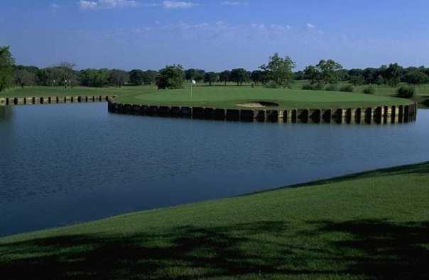 A view of a green surrounded by water at Tour 18 Dallas.