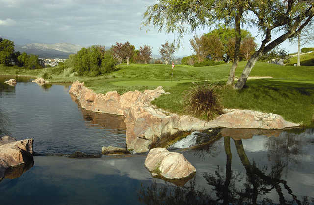 A view of a green surrounded by water at Spanish Hills Golf & Country Club.