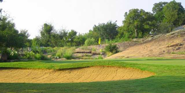 A view of a green with a bunker in foreground at Lighthouse Country Club