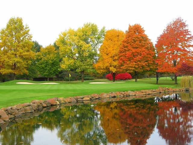 A view of a green surrounded by autumn trees at Elcona Country Club.