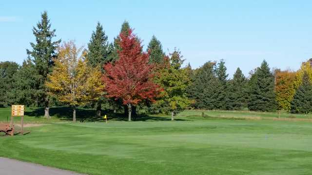 A view of a green with fall color trees in background at Whispering Pines Golf Course.