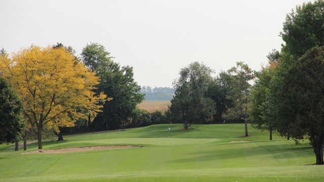 A view of a hole guarded by bunkers and a fall golden tree at Monroe Country Club.