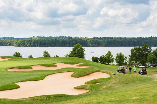 A view of elegant bunkers protecting a hole with the Cole Reservoir in backgound at Heron Bay Golf & Country Club.