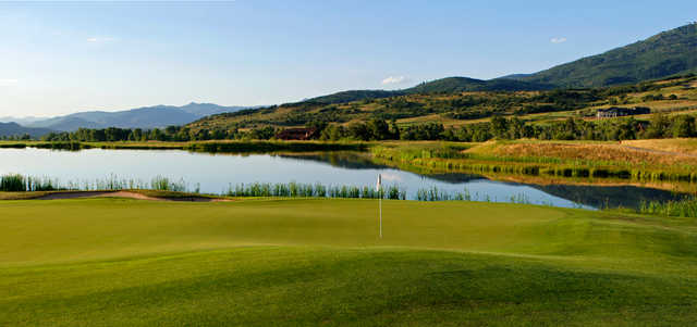 A view of a green with a pond in background at Catamount Ranch and Club.