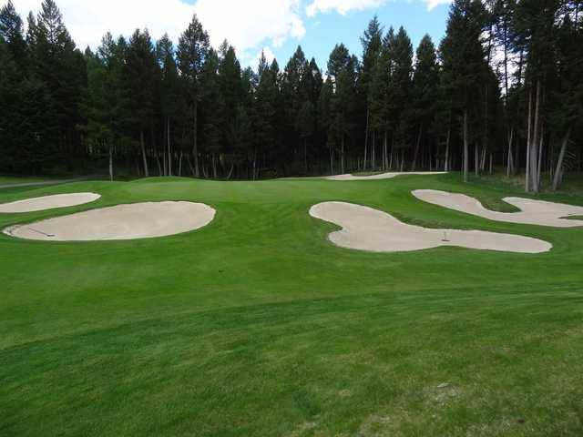 A view of a green protected by a collection of tricky bunkers at Crystal Lakes Golf Course.