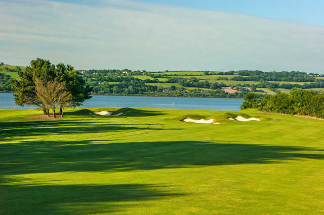 A view of a green with water in background at Cork Golf Club.