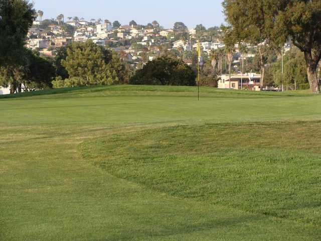 A view of a green and houses in the distance at Mission Bay Golf Course.