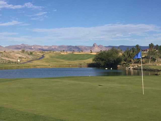 A sunny day view of a hole at Los Lagos Golf Club.