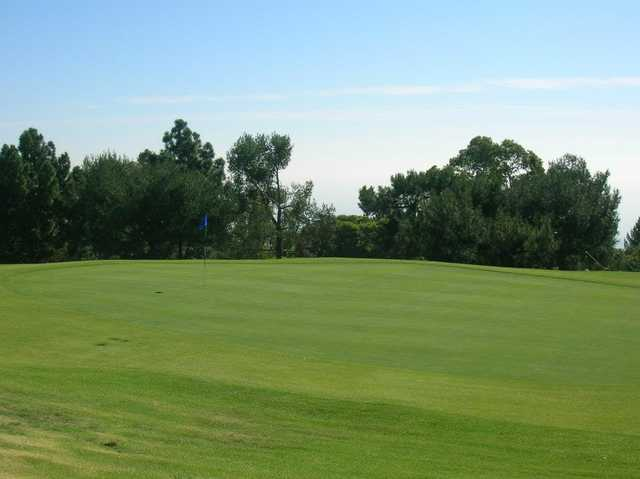 A sunny day view of a hole at Los Verdes Golf Course.