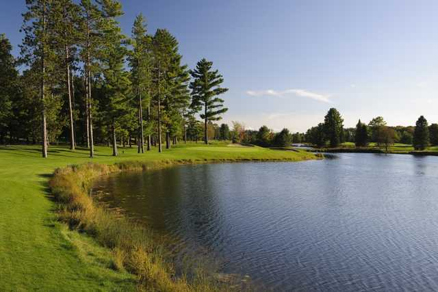 The sixth hole on the Reflections Course at Garland Lodge & Resort is bordered by a large pond to the right with bunkers protecting the right front and back of the green.