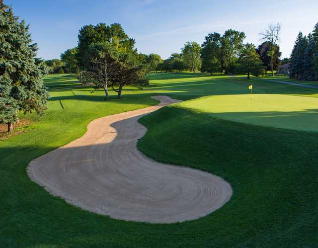 A view of a green protected by an elegant bunker at Mt. Prospect Golf Club.