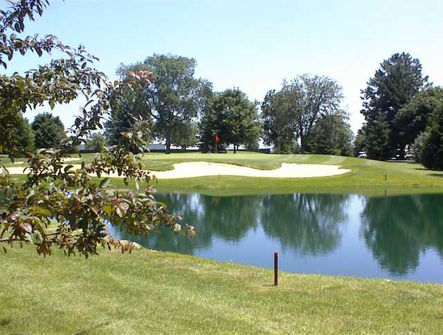 A view of a green surrounded by a tricky bunker and water at University of Illinois Golf Course.