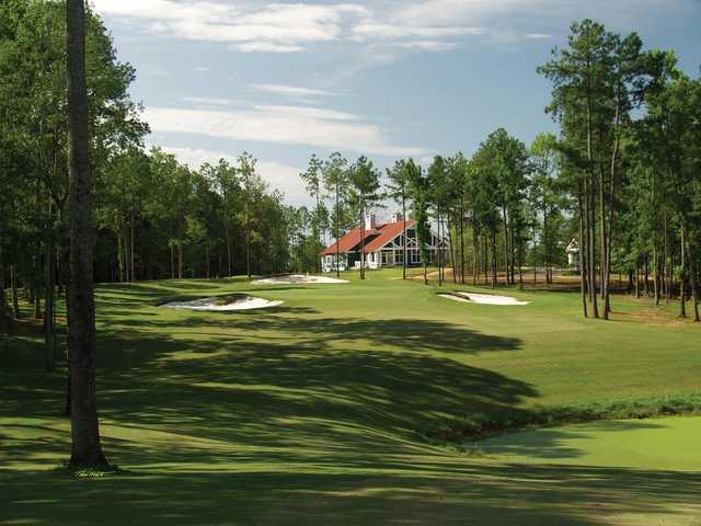 A view of a green surrounded by bunkers and the clubhouse in background from Arrowhead Pointe At Lake Richard B. Russell.