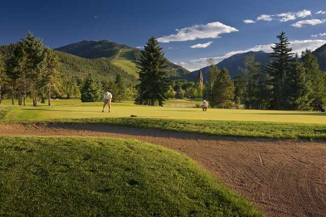 A sunny day view of a green at Aspen Golf Course.