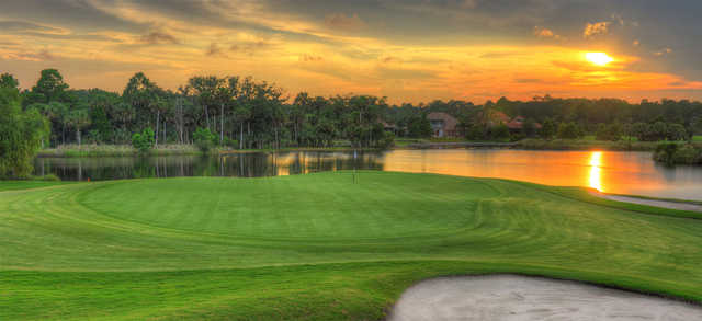 A view of a green with water in background at Plantation Bay Golf and Country Club.