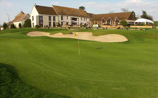 A view of a hole and the clubhouse at Stade Francais Courson Golf Club.