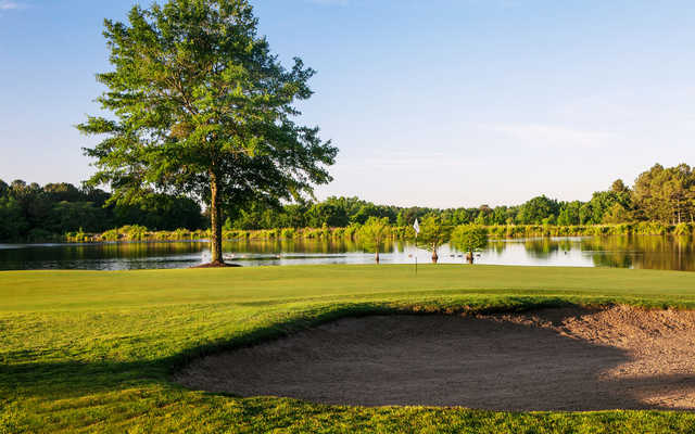 A view of a green with water in background at Summer Grove Golf Club.