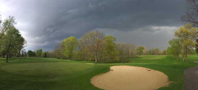 A spring day view of a hole covered by dark clouds at Meshingomesia Country Club.