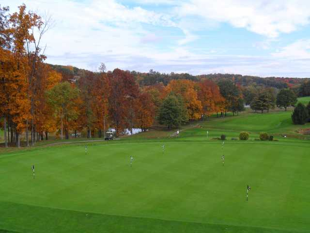 A fall day view of the practice putting green and a fairway in the distance at Seven Oaks Country Club.