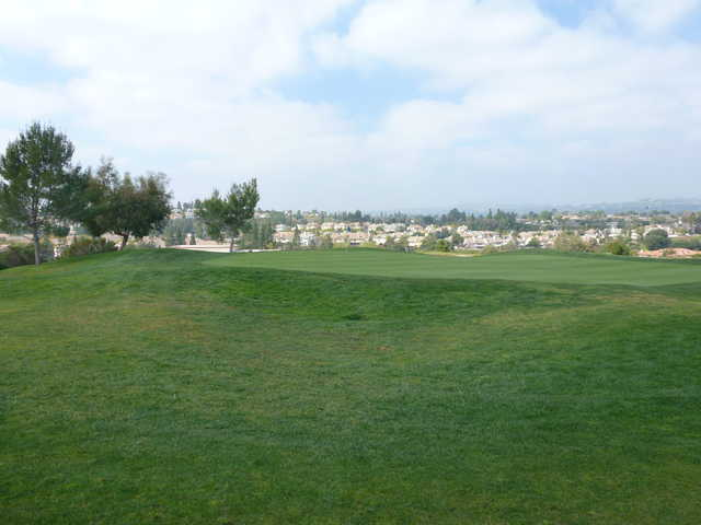 A view of a green with houses in the distance at Westridge Golf Club.