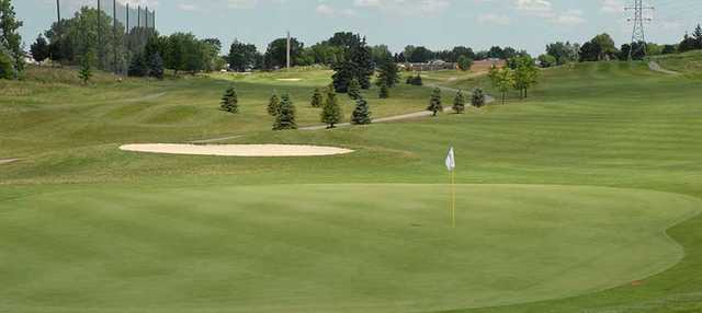 A sunny day view of a hole at Red Oaks Golf Course.