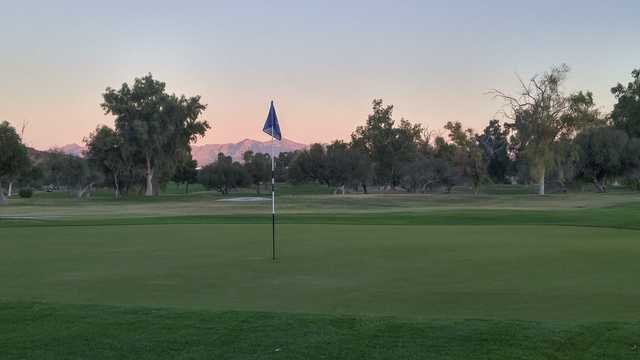 A sunset view of a green from Tres Rios Golf Course at Estrella Mountain Park.